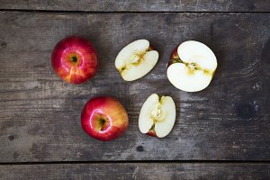Ripe red apples and slices on dark