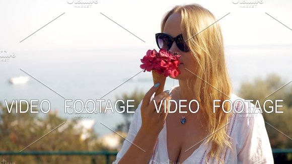 Young Woman Smelling Red Flowers In Waffle Cone