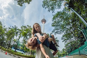 happy family makes selfie in the background of the Minar tower in Kuala Lumpur