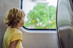 Beautiful toddler boy looking out train window outside, while it moving. Going on vacations and traveling by railway in summer