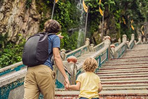 Father and son in the background of Batu Caves, near Kuala Lumpur, Malaysia. Traveling with children concept