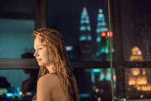 Beautiful woman wipes her hair after a shower on the background of a window with a panoramic view of the night city