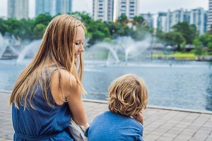 Happy mom with little son enjoying water fountains