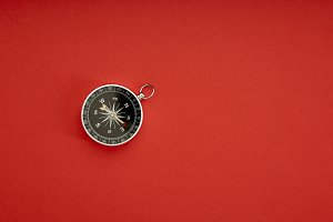compass on red background top view