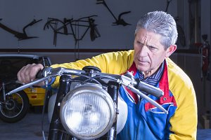 male mechanic starting a motorbike