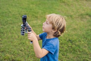 Little boy shoots a video on an action camera against a background of green grass