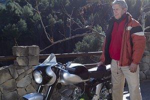 man standing beside a motorbike