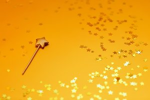Gold star candle on a gold background with stars