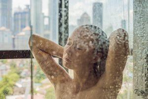 Beautiful woman in the shower behind glass with drops on the background of a window with a panoramic view of the city