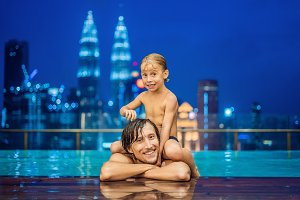 Father and son in outdoor swimming pool with city view in blue sky