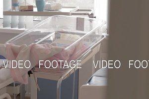 Baby bassinet near sleeping mother in maternity hospital