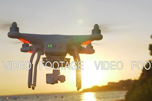 Drone flying near the sea at sunset