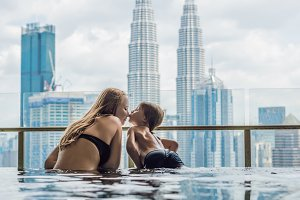 Mother and son in outdoor swimming pool with city view in blue sky