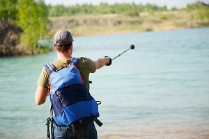 Photo from back of male tourist pointing with stick for walking forward against backdrop of lake and green bushes