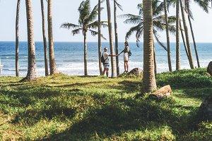 Young couple among palms on the tropical island of Bali.