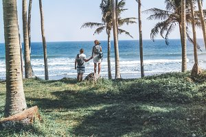 Young couple among palms on the tropical island of Bali.