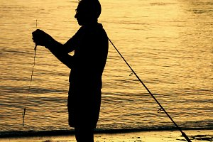 fisherman on the beach at dusk