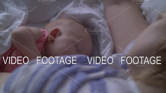 Woman Breasfteeding Baby Lying In Bed