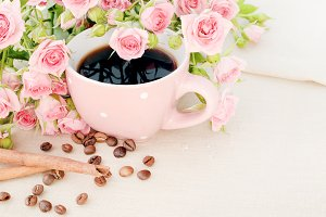 Cup of black coffee and red rose