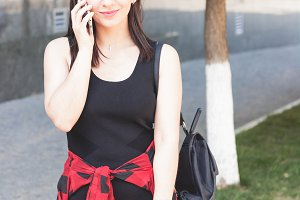 Attractive brunette female student talking on mobile phone.