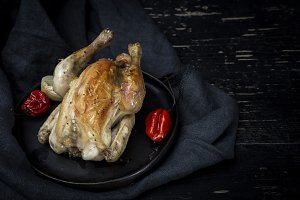 Roast chicken on black table