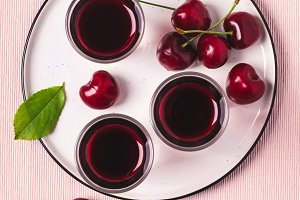 Cherry alcohol drink liquor or brandy on pink background