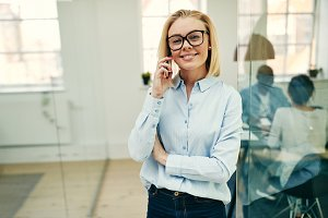 Smiling businesswoman standing in an office talking on her cellphone
