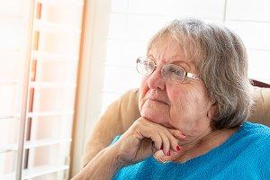 Sad Senior Woman Gazing Out Window