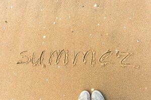 Summer written on the beach sand