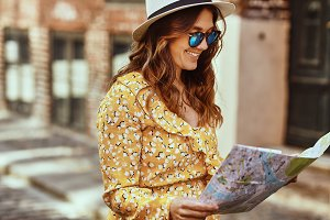 Smiling woman walking through cobblestone city streets with a map