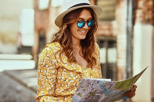 Smiling young woman using a map to explore cobblestone streets