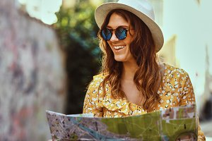 Smiling young woman exploring city streets with a map