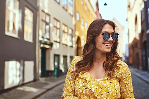 Smiling young woman wearing sunglasses exploring city streets