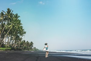 Young woman is spinning on a black sand beach, Bali island.