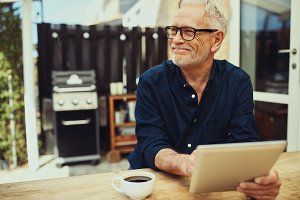 Smiling senior man sitting outside with a coffee and tablet