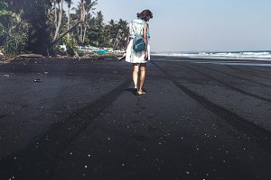 Young woman on a black sand beach, Bali island.