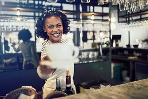 Smiling cafe barista holding a cup of freshly brewed coffee