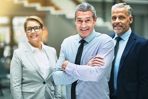 Smiling mature businessman standing with colleagues in an office