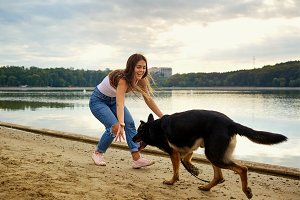 A girl is playing with her dog in the park on the summer beach.