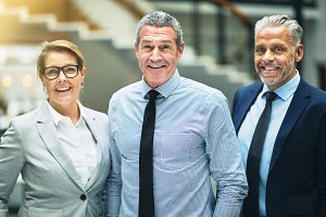 Mature businessman and smiling colleagues standing together in an office