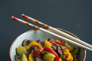 Traditional asian salad with meat and vegetables. Black background and copy space