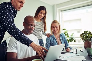 Smiling diverse businesspeople talking together over a laptop