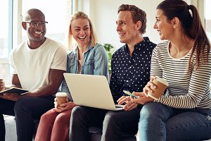 Laughing diverse businesspeople sitting and talking together an office