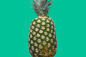 Fresh pineapple on the green colorfurful background