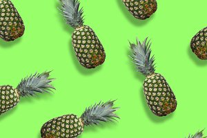 Fresh pineapples on the green colorfurful background