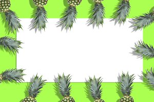 Fresh pineapples on bright green background. Horizontal orientation