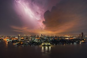 Thunder storm lightning strike over building area in Bangkok City at night, Thailand.