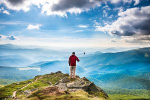 Young man on top of mountain