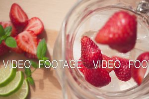 Sliced strawberries fall into a carafe with ice and water slow motion