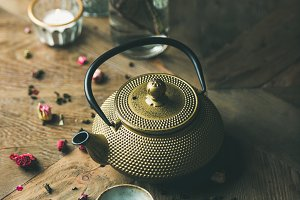 Golden iron teapot, cups, dried rose, candles, almond flowers
